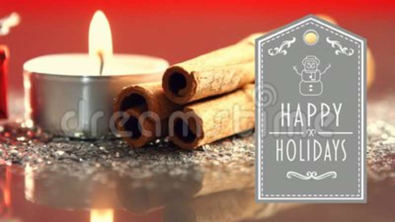 happy holidays text with gift lit candles and cinnamon sticks stock