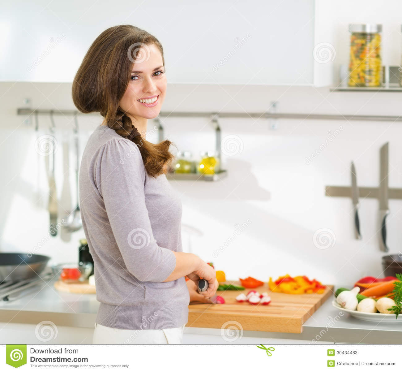 Happy housewife cutting fresh vegetables in kitchen stock for Modern housewife
