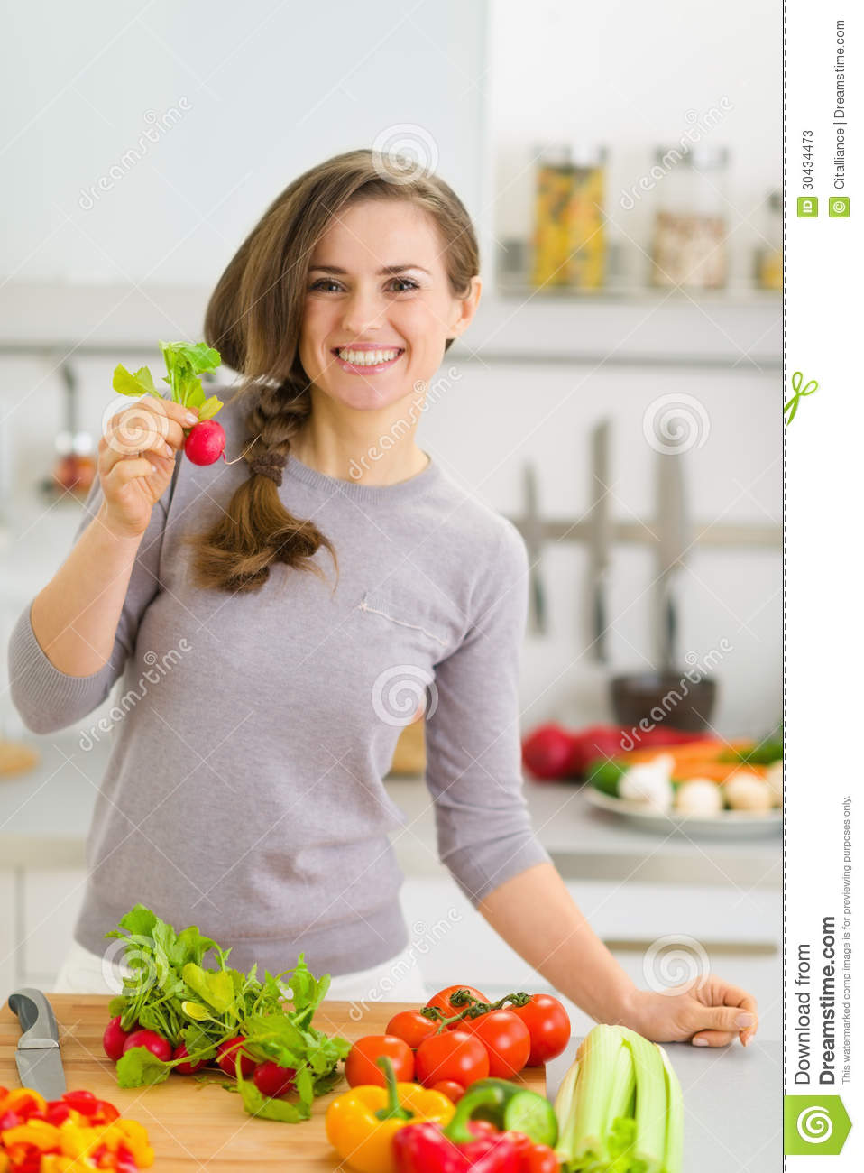 Happy housewife in kitchen showing radish stock photos for Modern housewife
