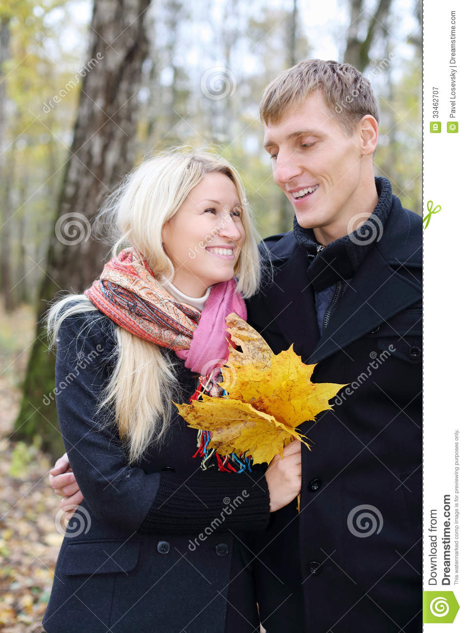 Happy husband and wife with yellow maple leafle look at other