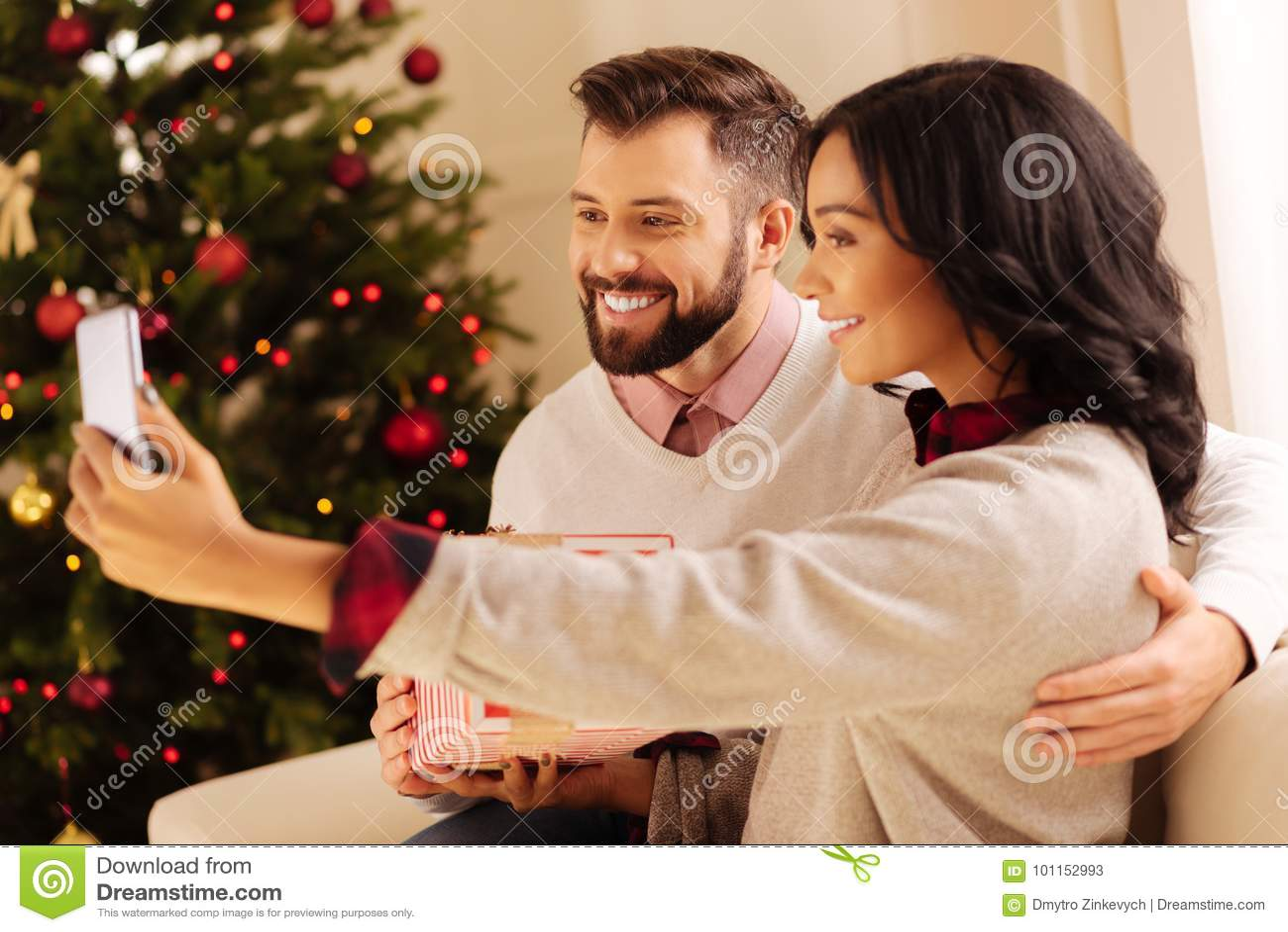 https://thumbs.dreamstime.com/z/happy-international-couple-taking-selfies-christmas-seizing-moment-happy-young-international-couple-sitting-sofa-101152993.jpg