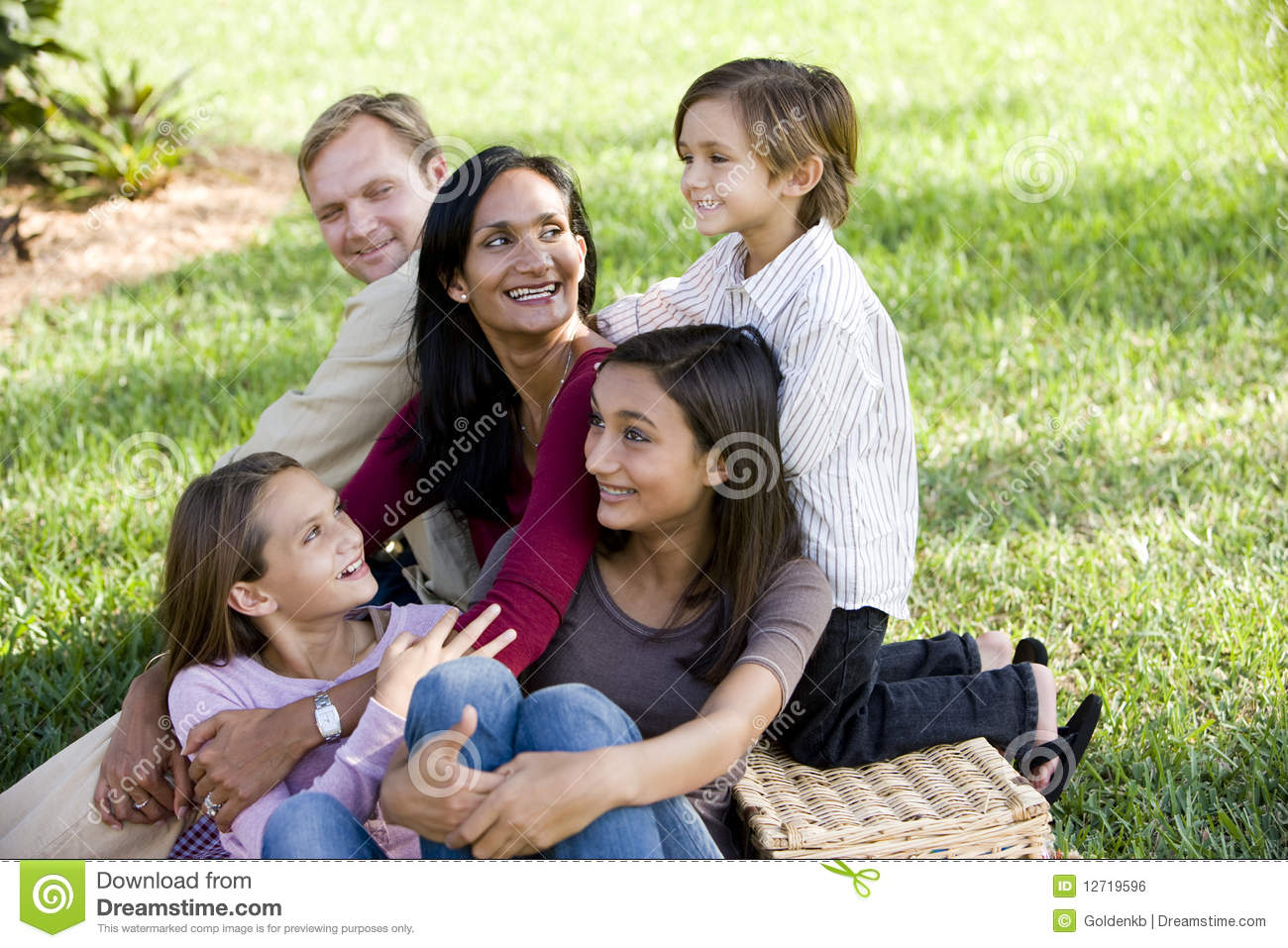 Happy interracial family of five enjoying a picnic