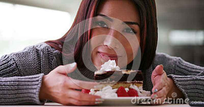 Happy Japanese woman eating cake at home