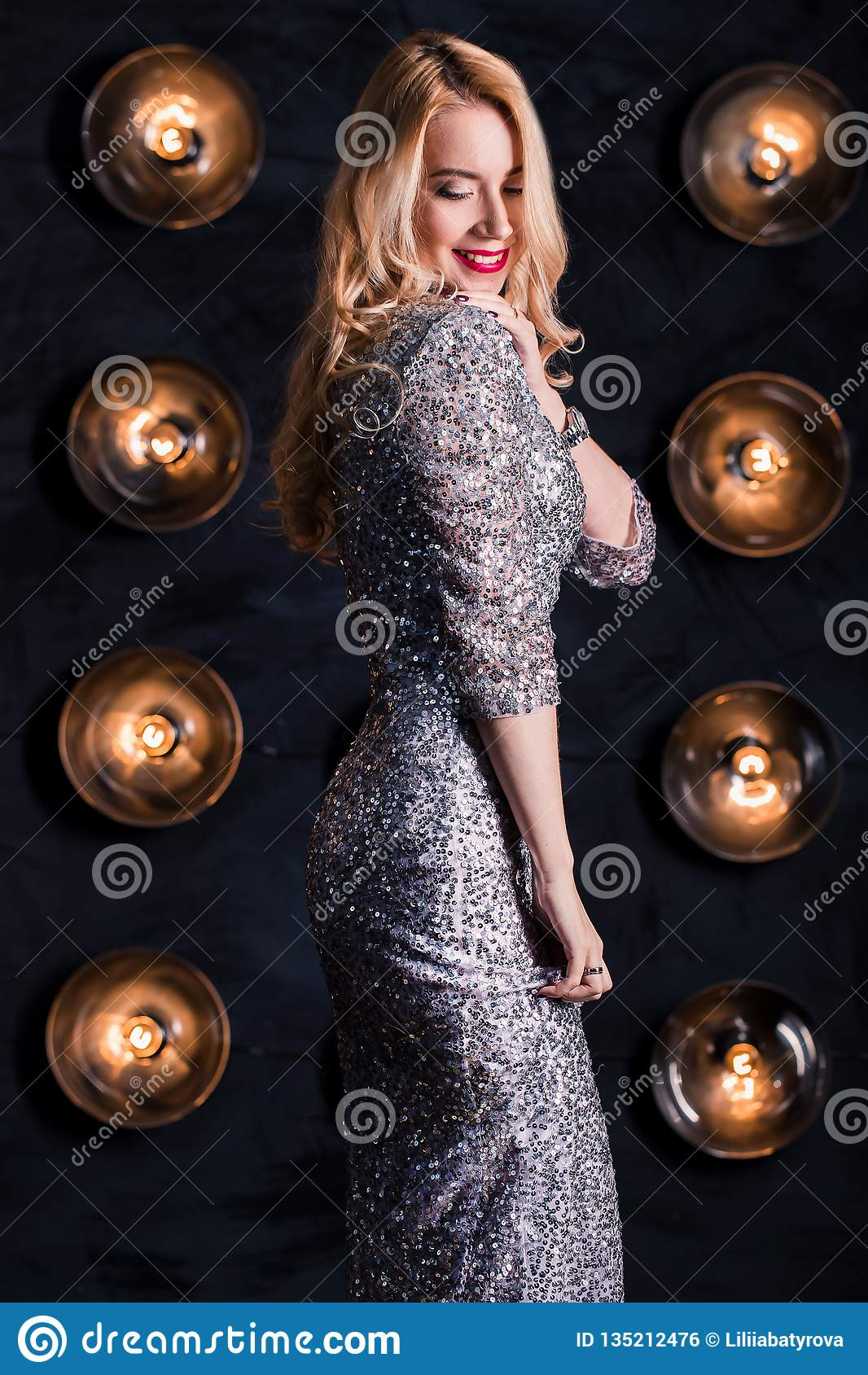 Happy joyful blond woman in a long silver dress on a black background. Celebration, party, new year