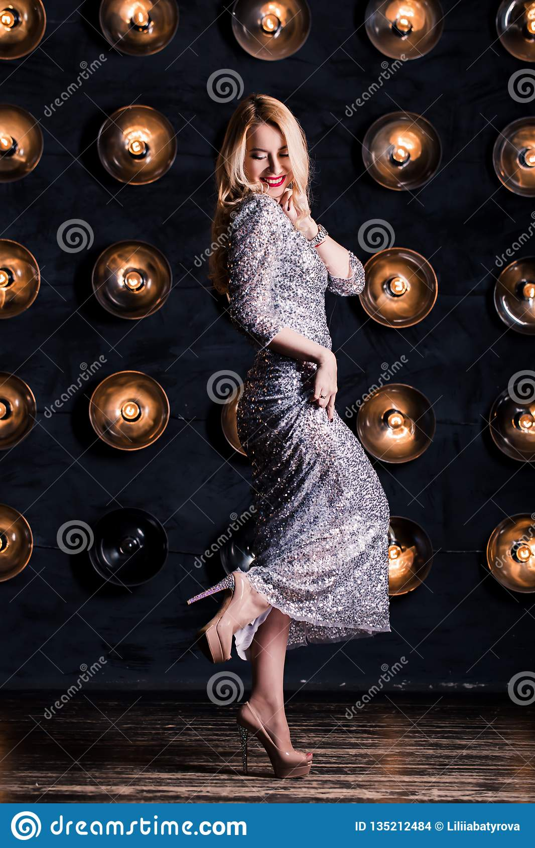 Happy joyful blond woman in a long silver dress on a black background. Celebration, party, new year, birthday