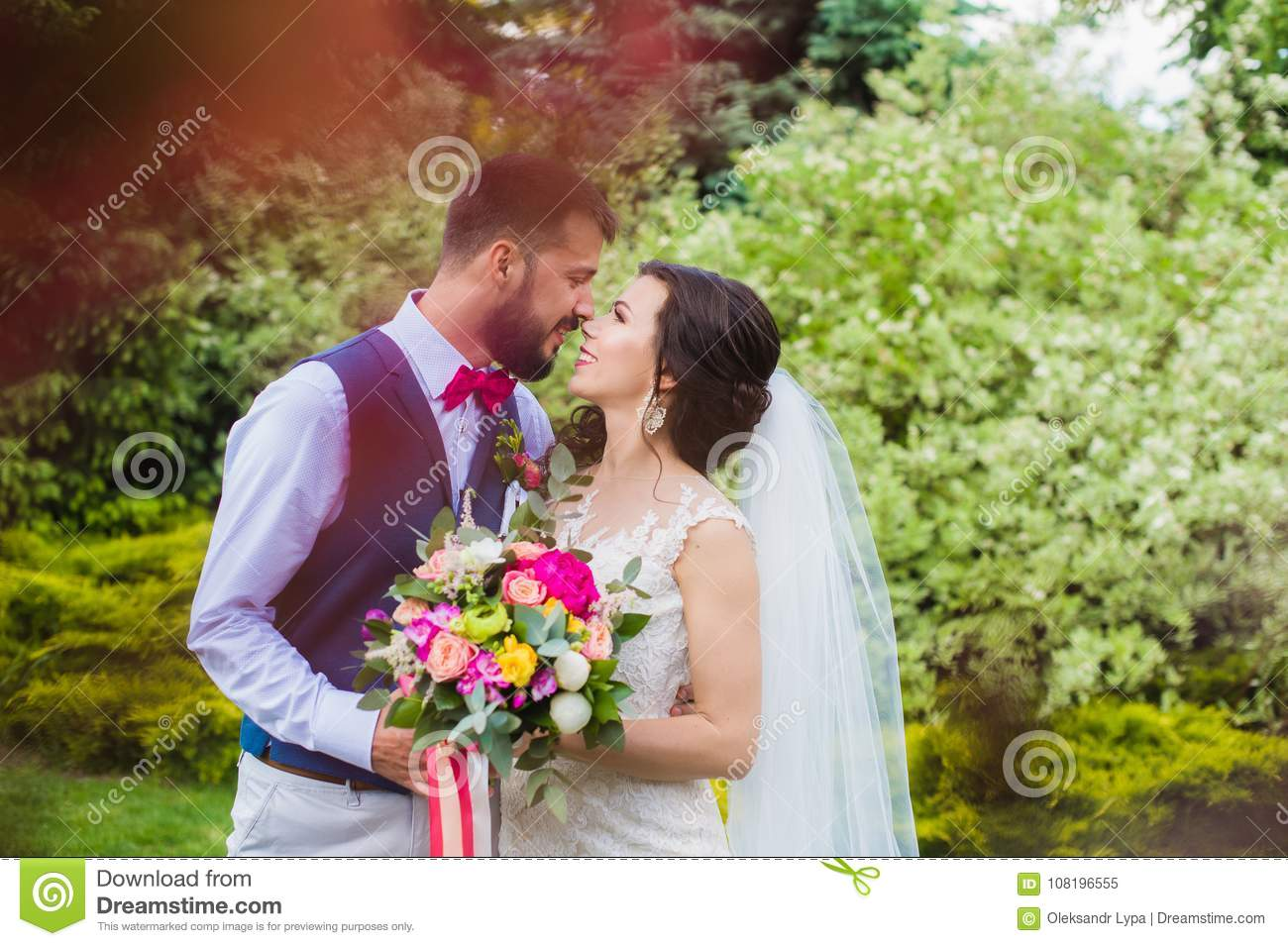 Happy just married couple kissing in the green garden beautiful stylish bride and groom became husband and wife posing in their wedding day