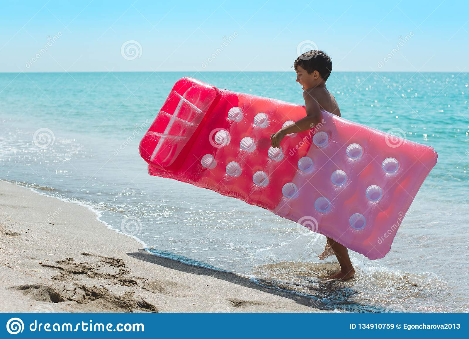 A happy kid carries a mattress along the surf line.
