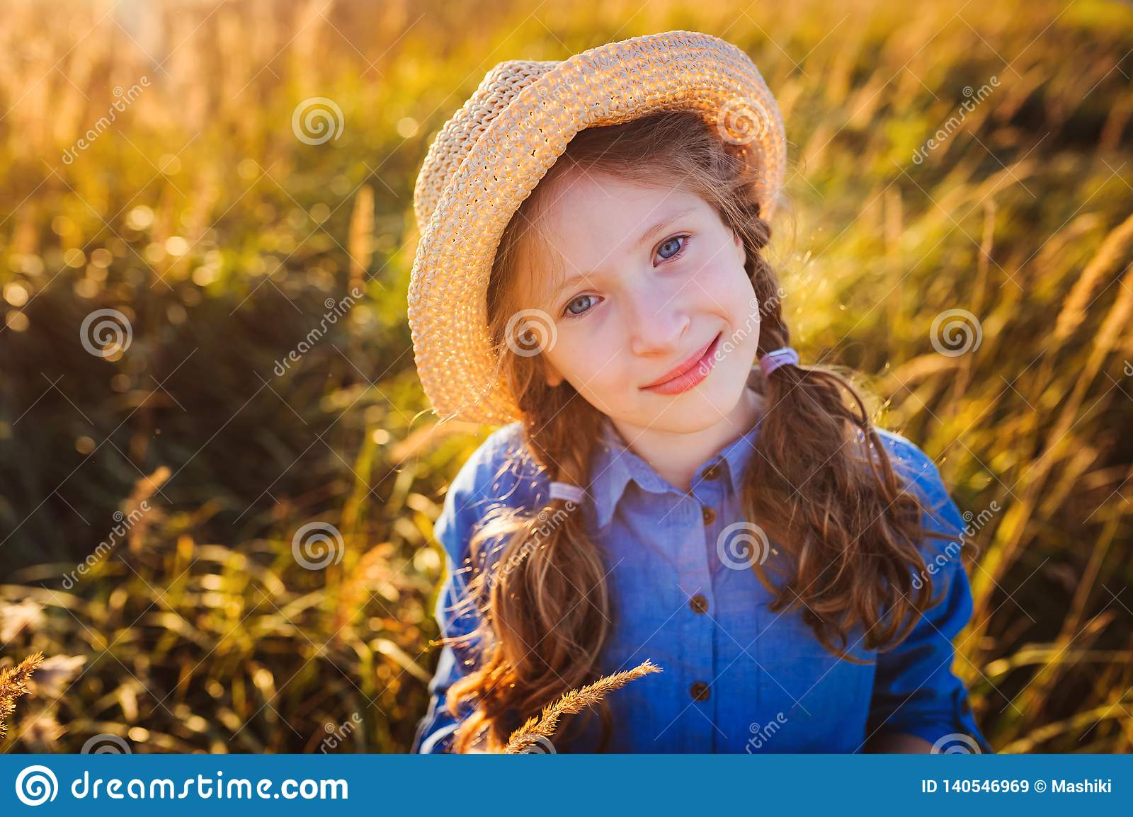 Happy kid girl in blue dress and straw walking on summer sunny meadow.