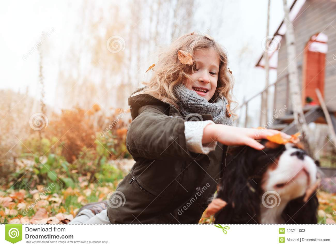 happy kid girl playing with her cavalier king charles spaniel dog in autumn