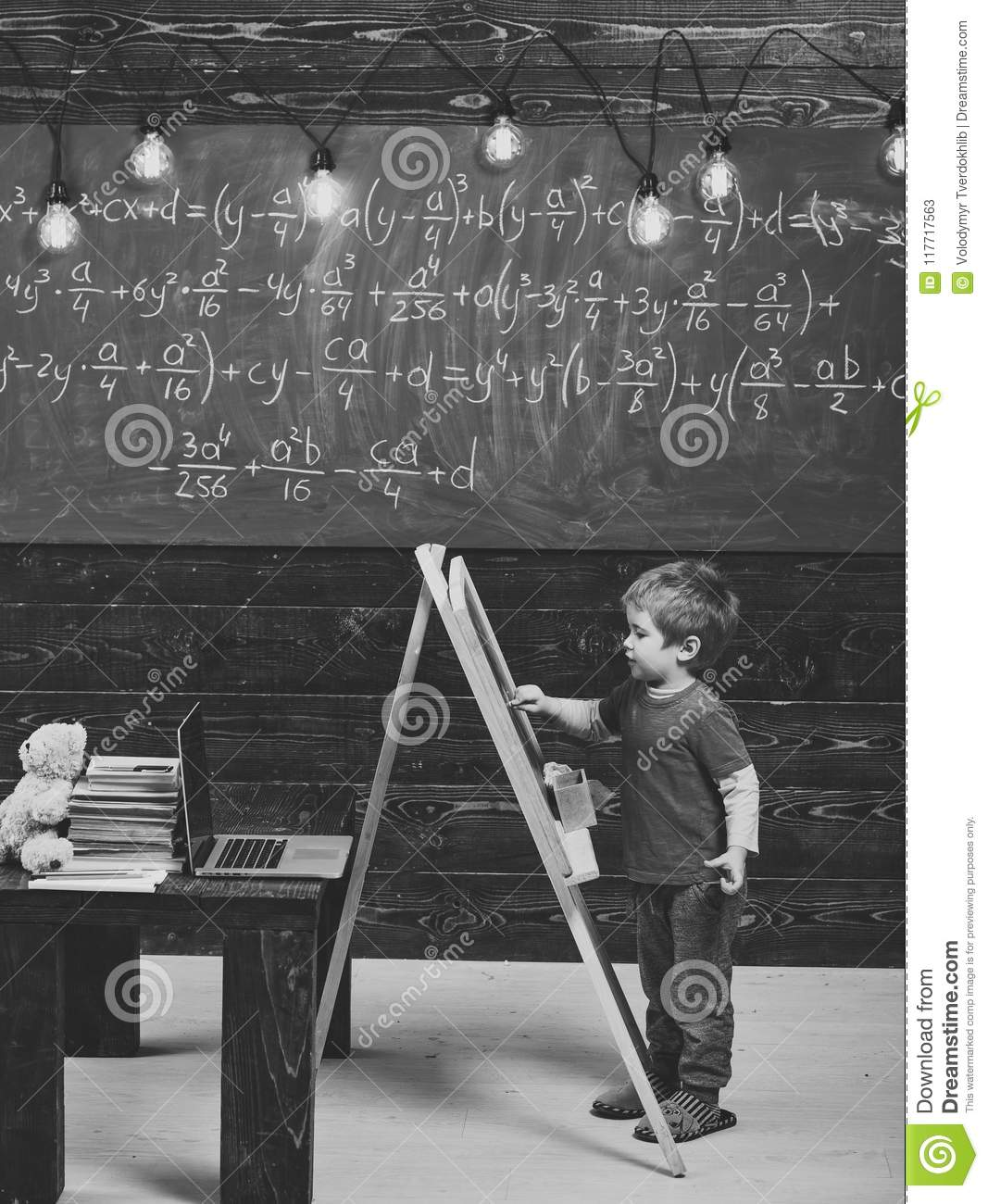 Happy kid having fun. Little boy writing on chalkboard. Side view kid in front of green board with math equation. Smart