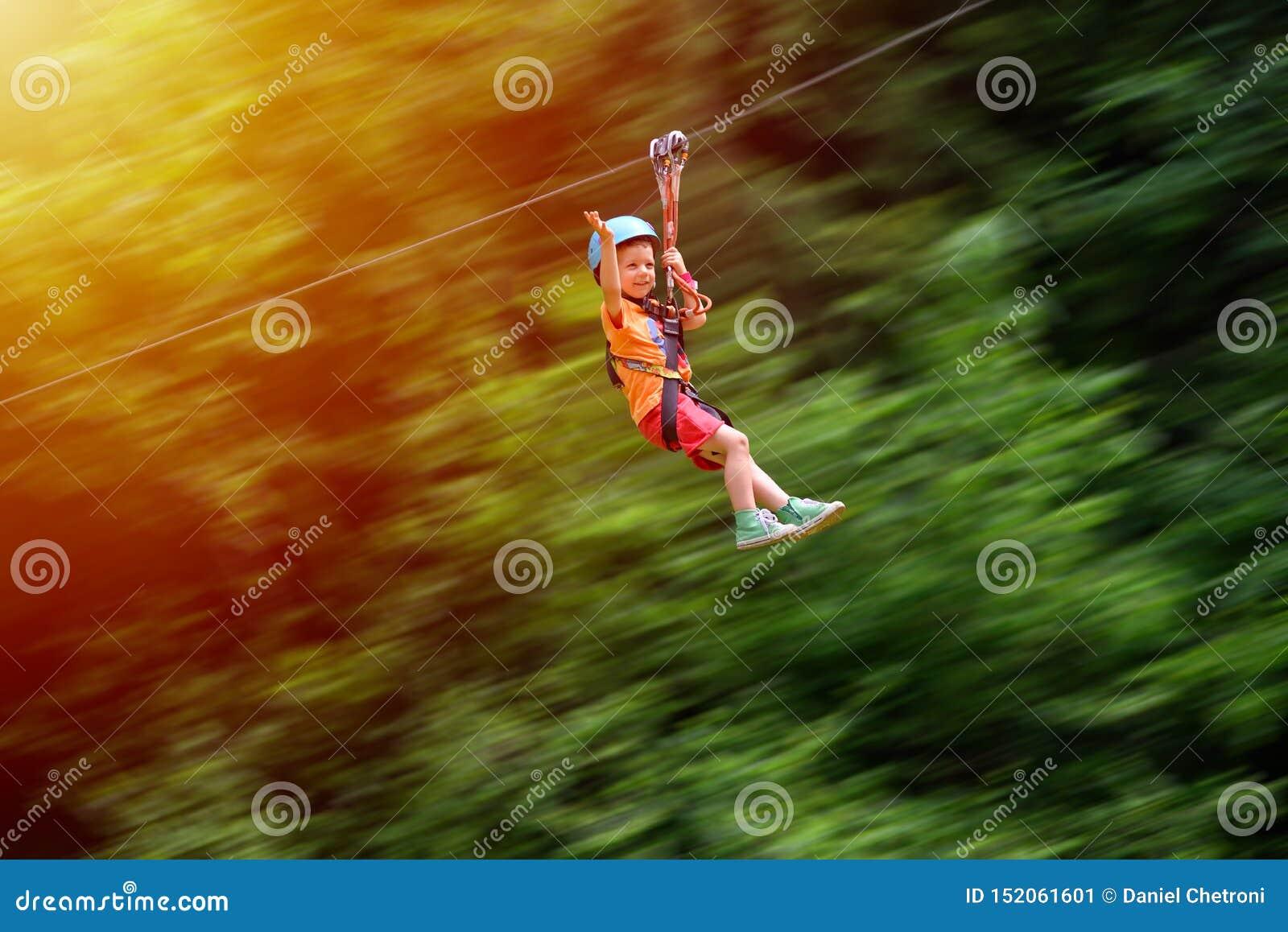 Happy kid with helmet and harness on zip line between trees. Panning effect