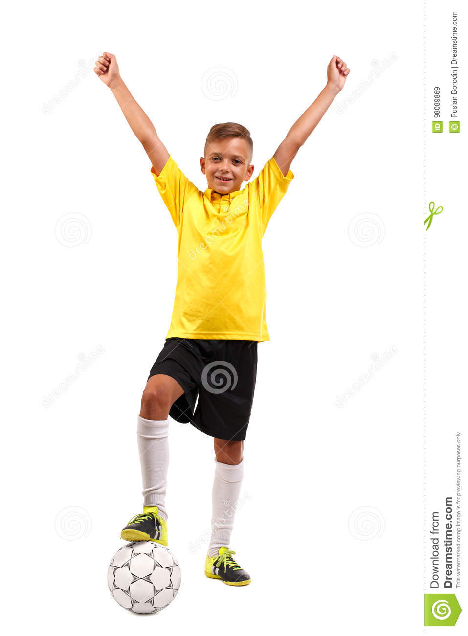 A happy kid with his leg on a soccer ball. A cheerful child in a football uniform isolated on a white background. Sports