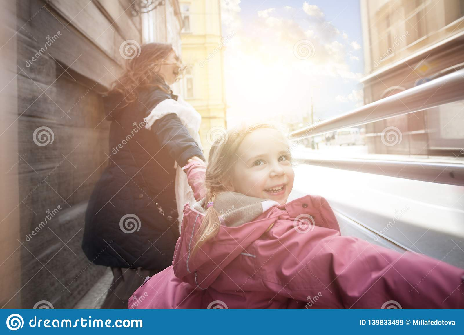 Happy kid laughing with mother outdoor, motion
