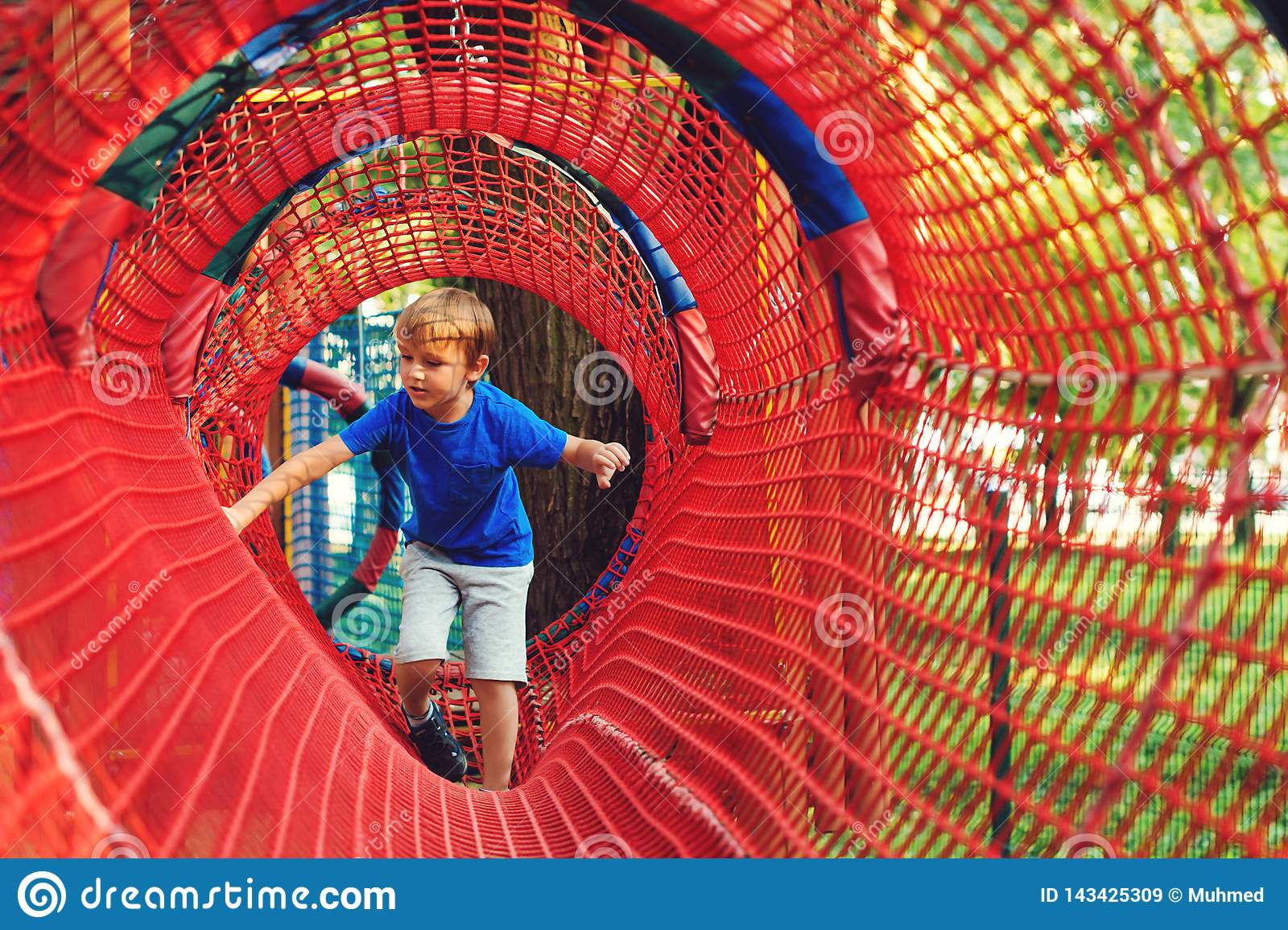 Happy kid overcomes obstacles in rope adventure park. Summer holidays concept. Little boy playing at rope adventure park. Modern