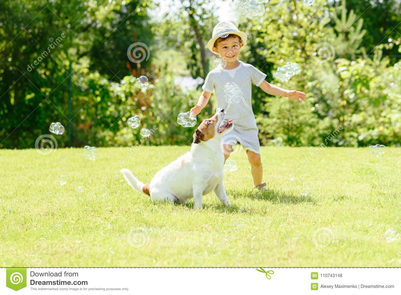 Happy Kid And Pet Dog Playing With Soap Bubbles At