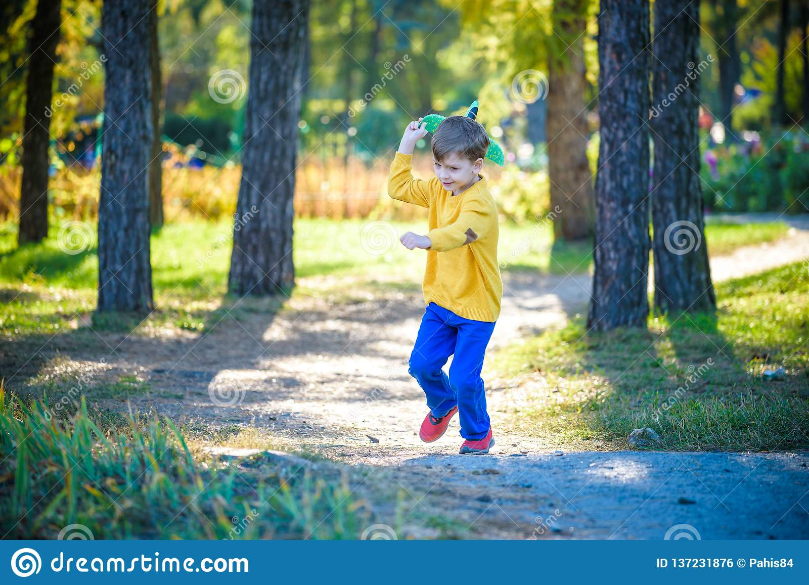Happy kid playing with toy airplane against blue summer sky background. Boy throw foam plane in the forest or park. Best childhood