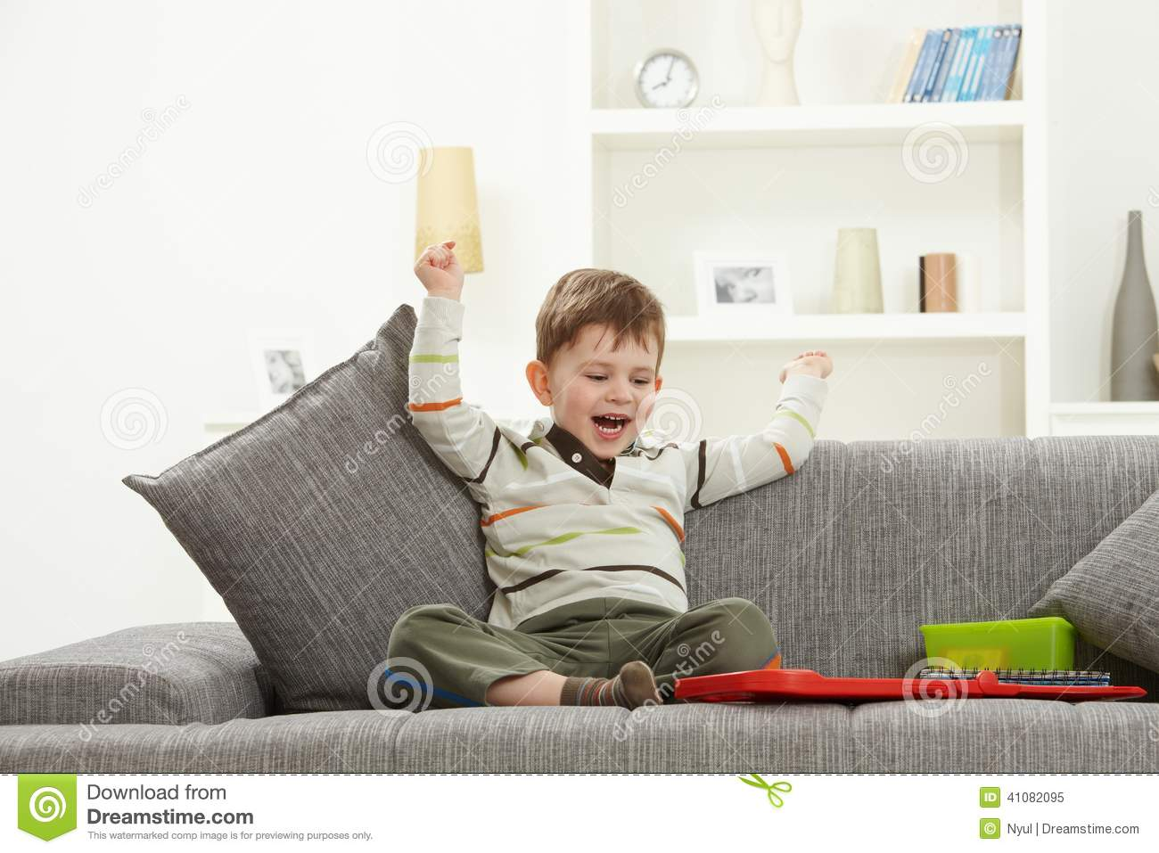 happy kid with toys sitting on sofa hands in air stock. Black Bedroom Furniture Sets. Home Design Ideas