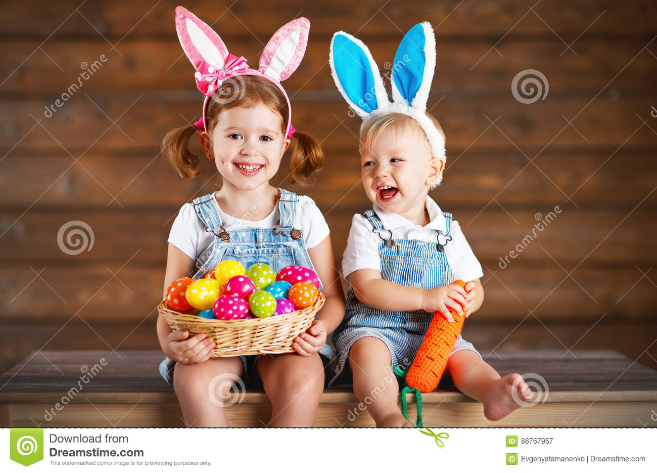 Happy kids boy and girl dressed as Easter bunnies with basket of