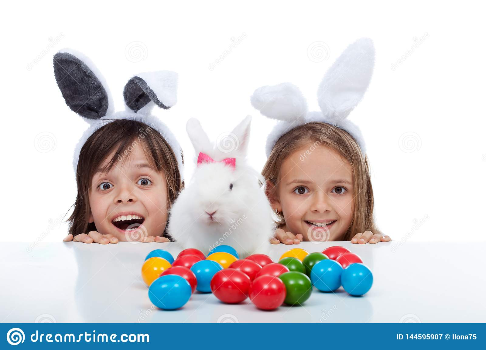Happy kids found the easter bunny and the eggs dying site - isolated on white