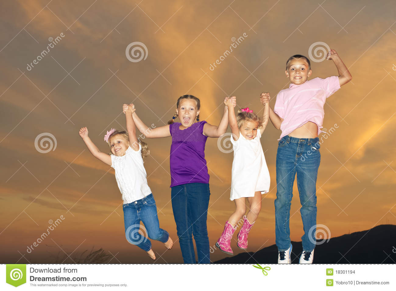 Four young children having fun together and jumping in the air