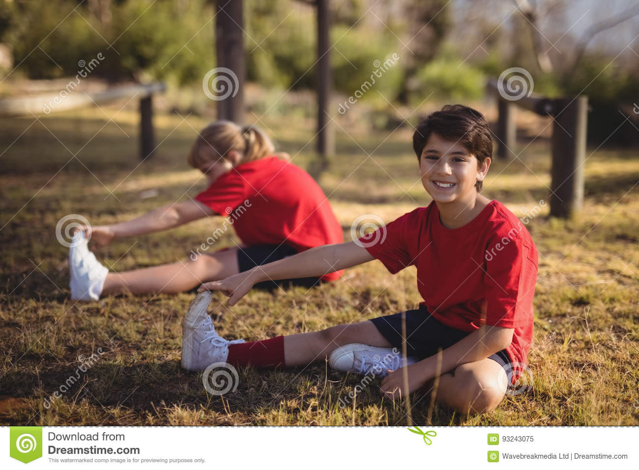Happy kids performing stretching exercise during obstacle course