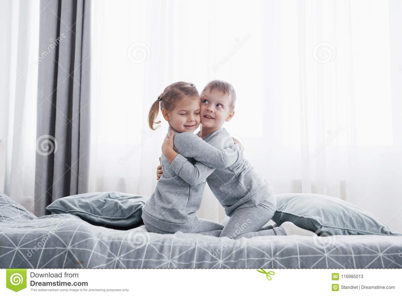 2ed612cfff Happy kids playing in white bedroom. Little boy and girl, brother and  sister play on the bed wearing pajamas. Nursery interior for children.