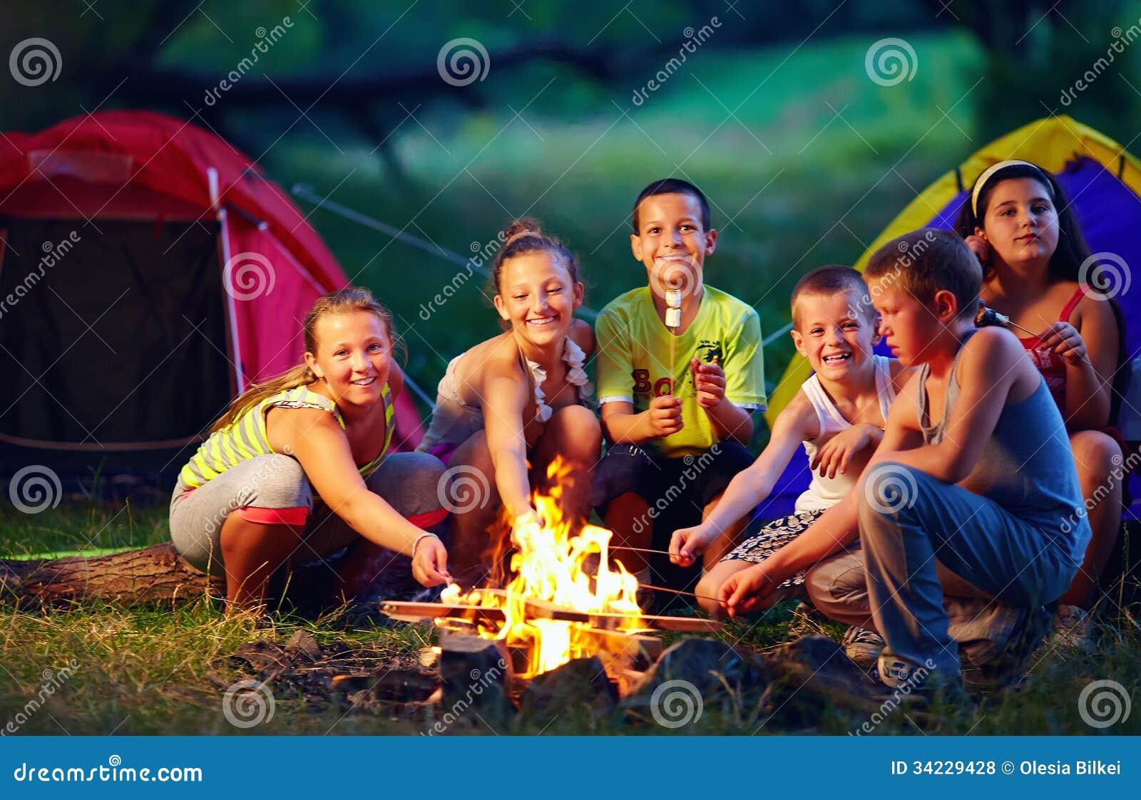 Happy kids roasting marshmallows on campfire