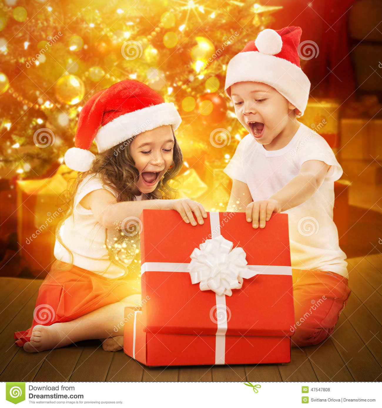 Happy Kids In Santa Hat Opening A Gift Box Stock Photo ...