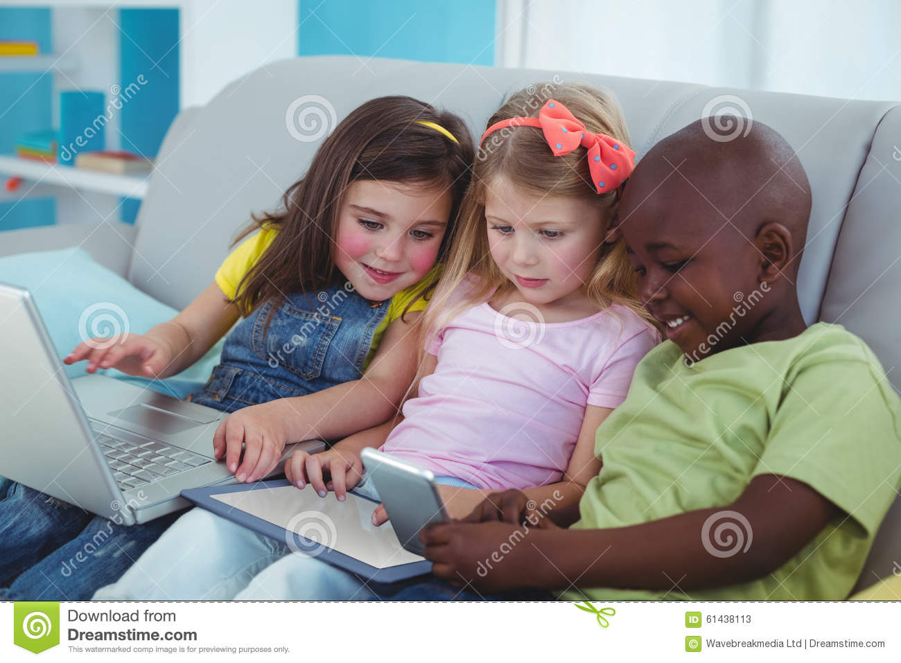 Happy kids sitting together with a tablet and laptop and phone on the