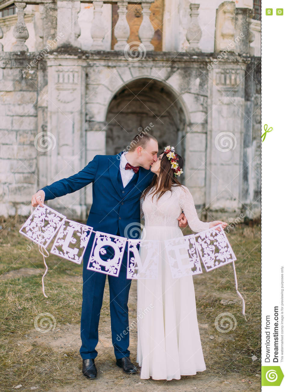 happy kissing bride and groom holding artistic papercut love letters