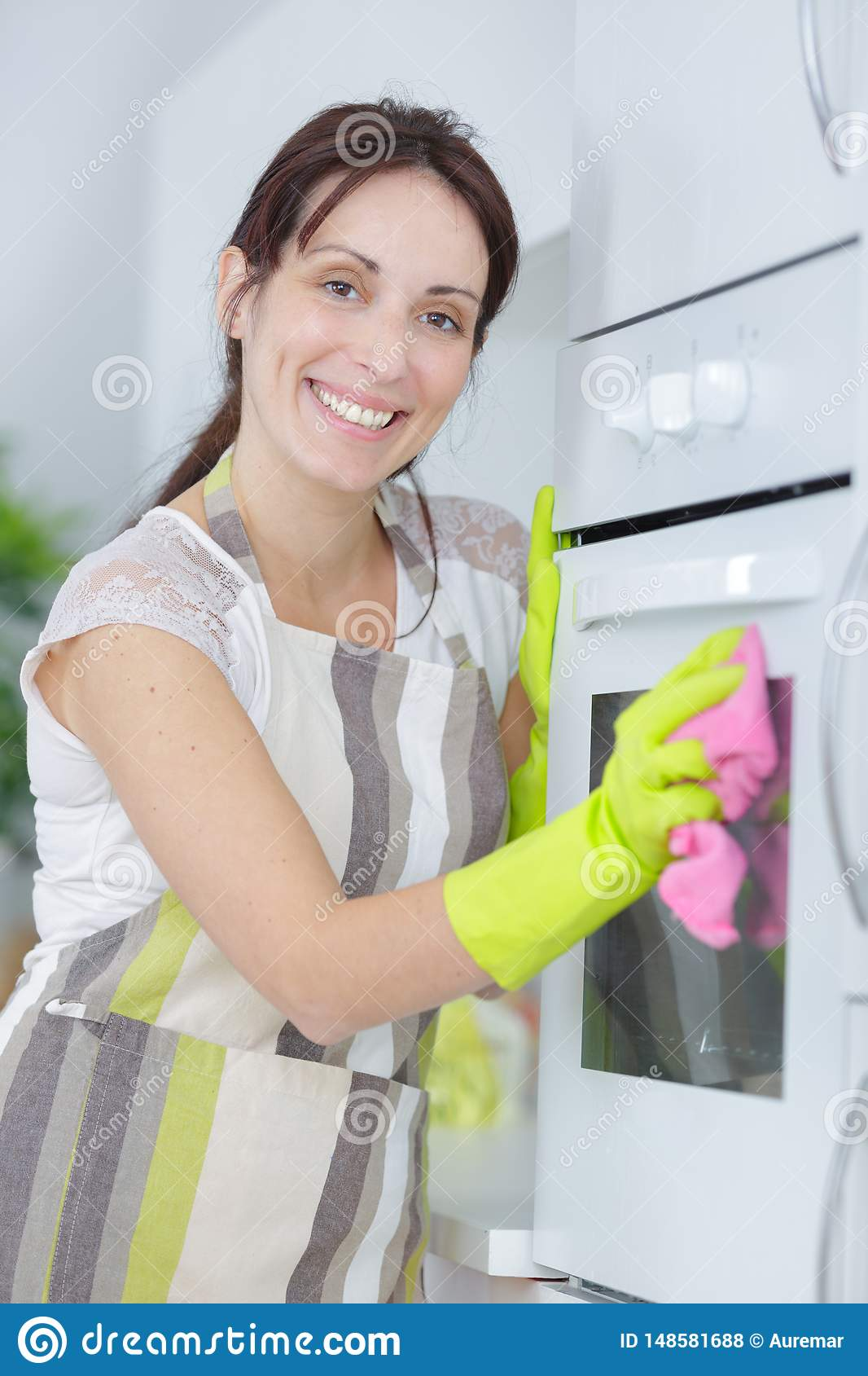 Happy lady cleaning oven