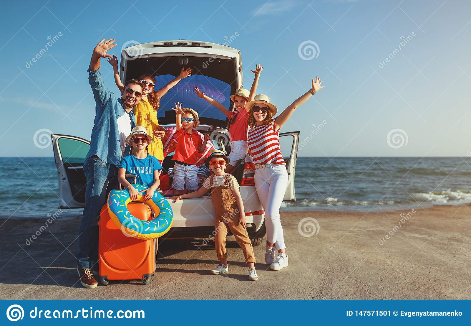 Happy large family  in summer auto journey travel by car on beach