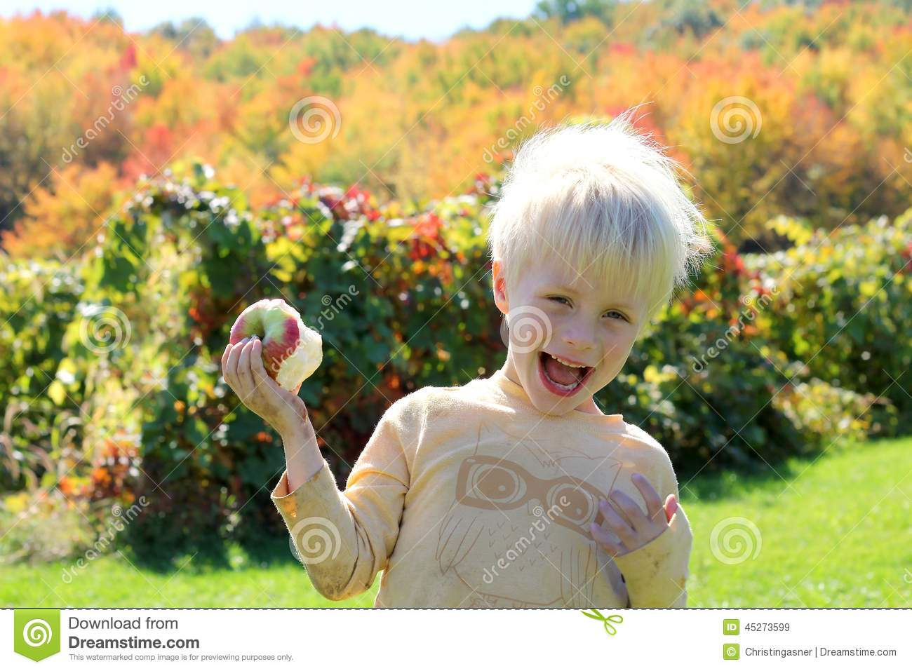 Happy Laughing Child Eating Apple at Orchard