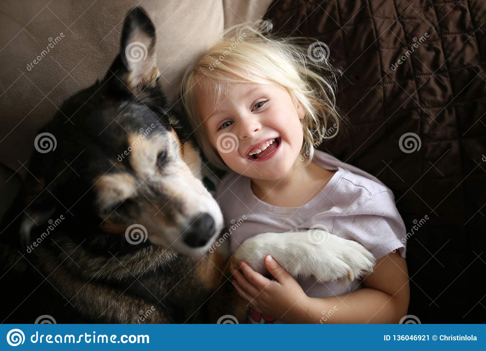 Happy, Laughing Little Girl Child Hugging Pet Dog on Couch