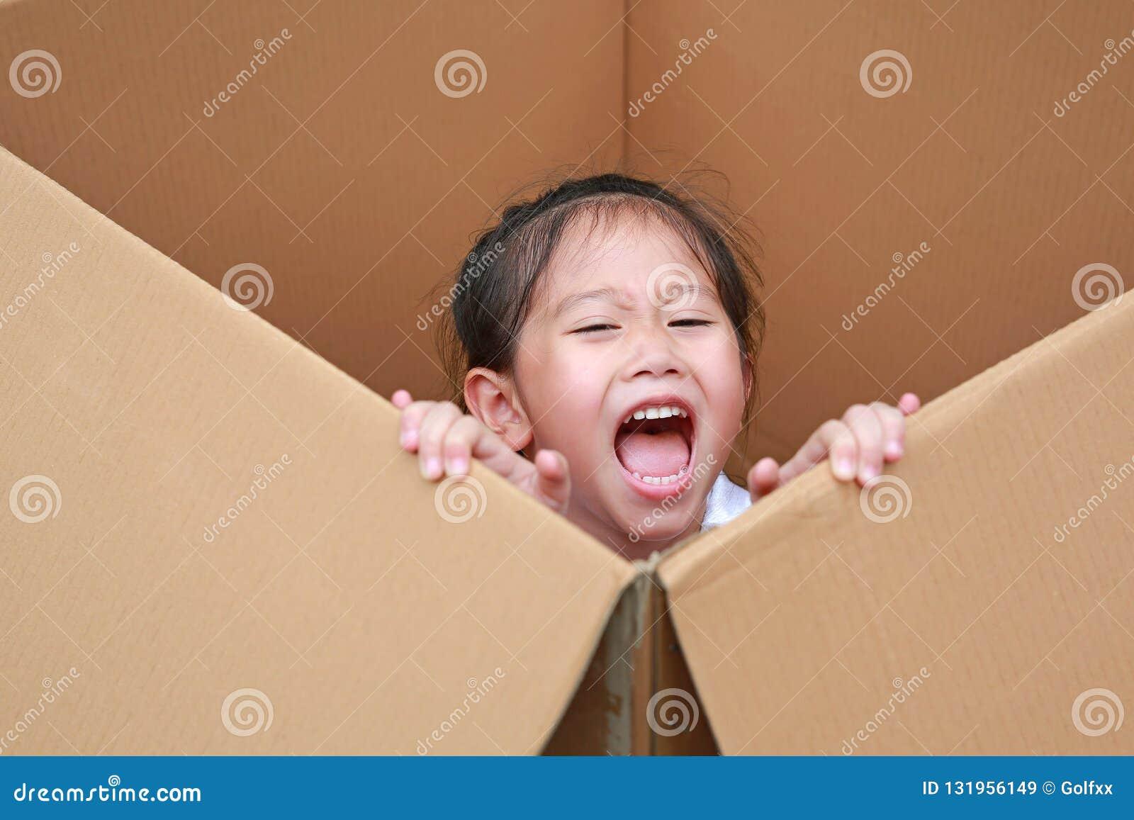 Happy little Asian child girl playing peekaboo and lie in big cardboard box
