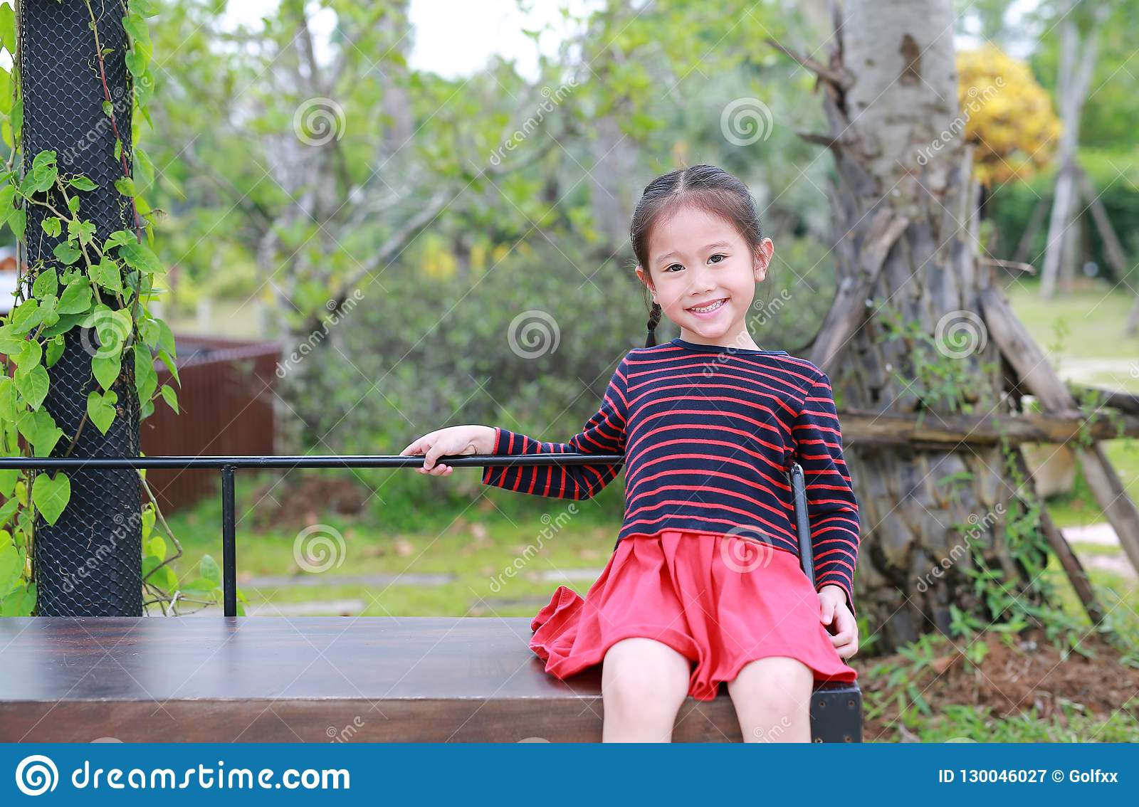 Happy Little Asian Child Girl Sitting On Wood Bench In The