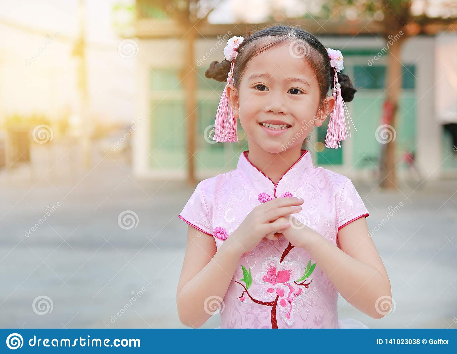 Happy little Asian child girl wearing pink traditional Chinese dress with greeting gesture celebration for Chinese New Year