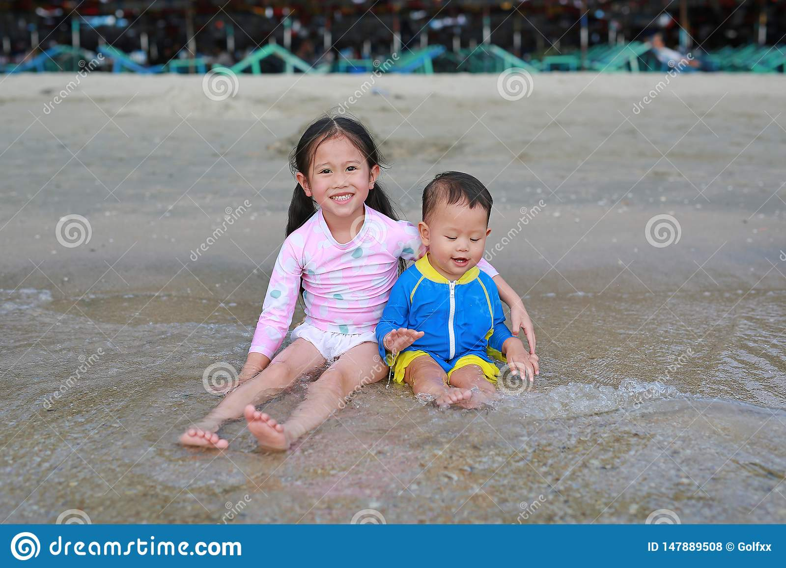 Happy little Asian sister and her little brother in swimming suit sitting and playing sea waves on the beach