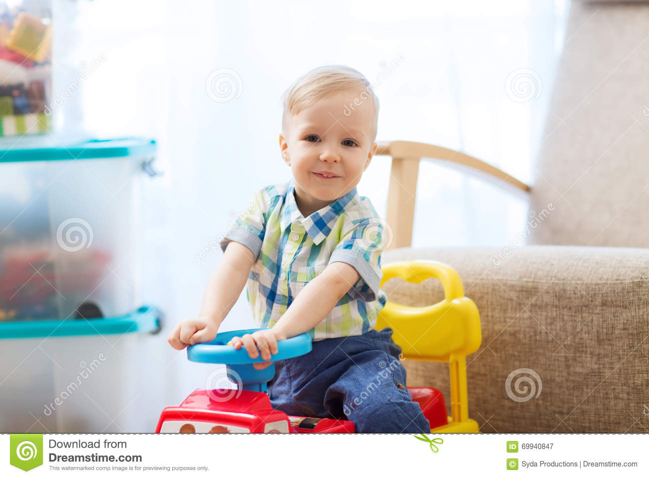 Boy Ride On Toys : Happy little baby boy driving ride on car at home stock