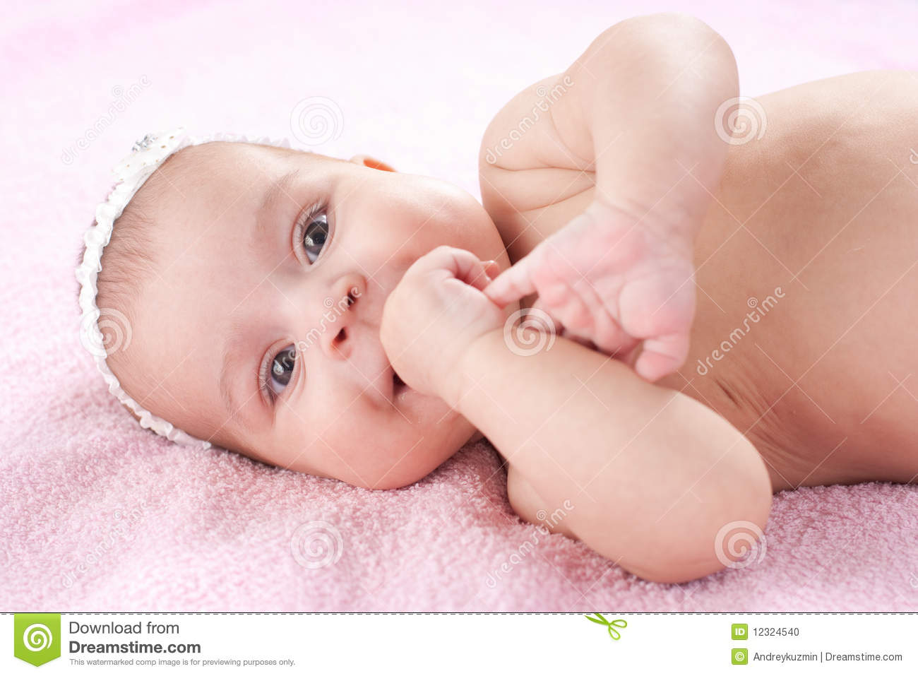 Happy Little Baby Girl Lying With Hand In Mouth Stock Photo Image