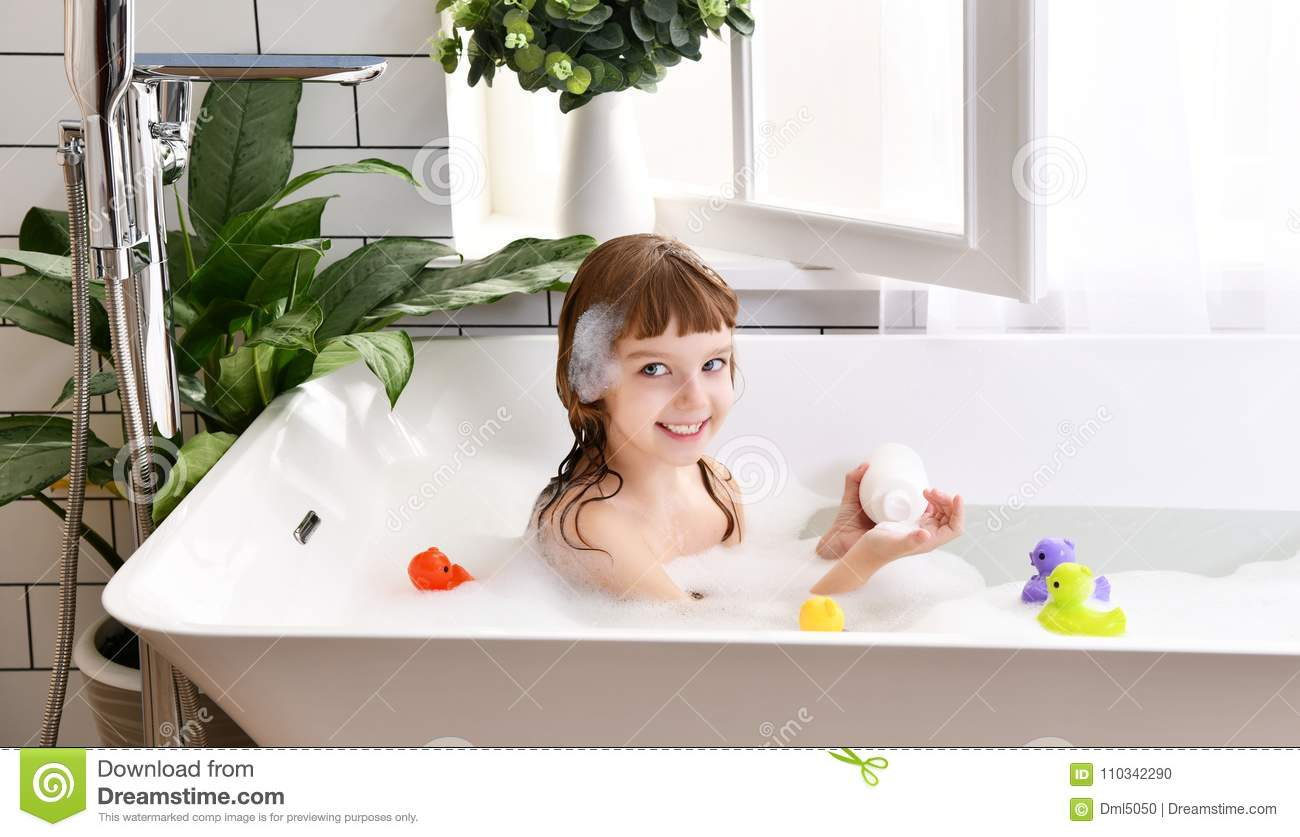 Happy Little Baby Girl Sitting In Bath Tub Play With Yellow Duck Toy ...