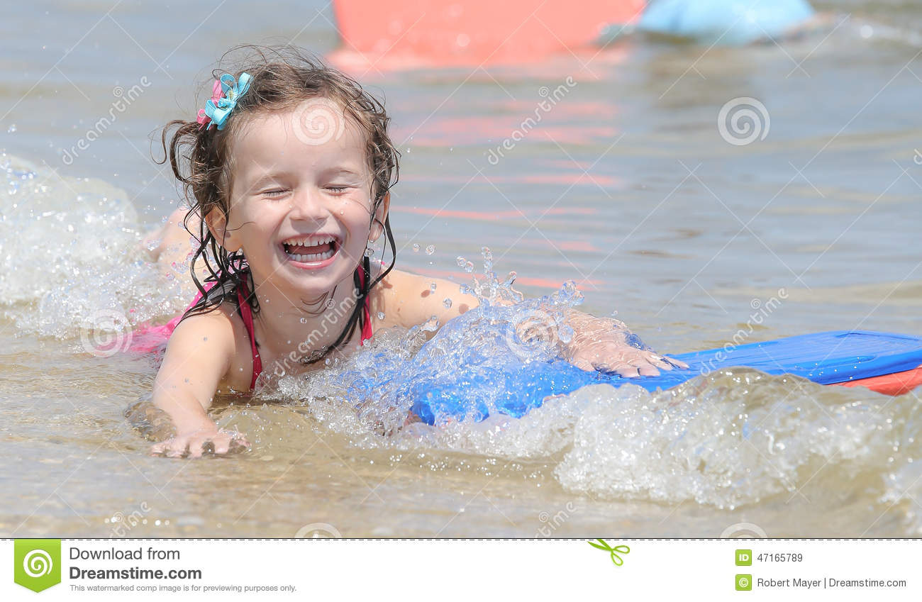 young brown haired little child girl swimming in a lake and smiling