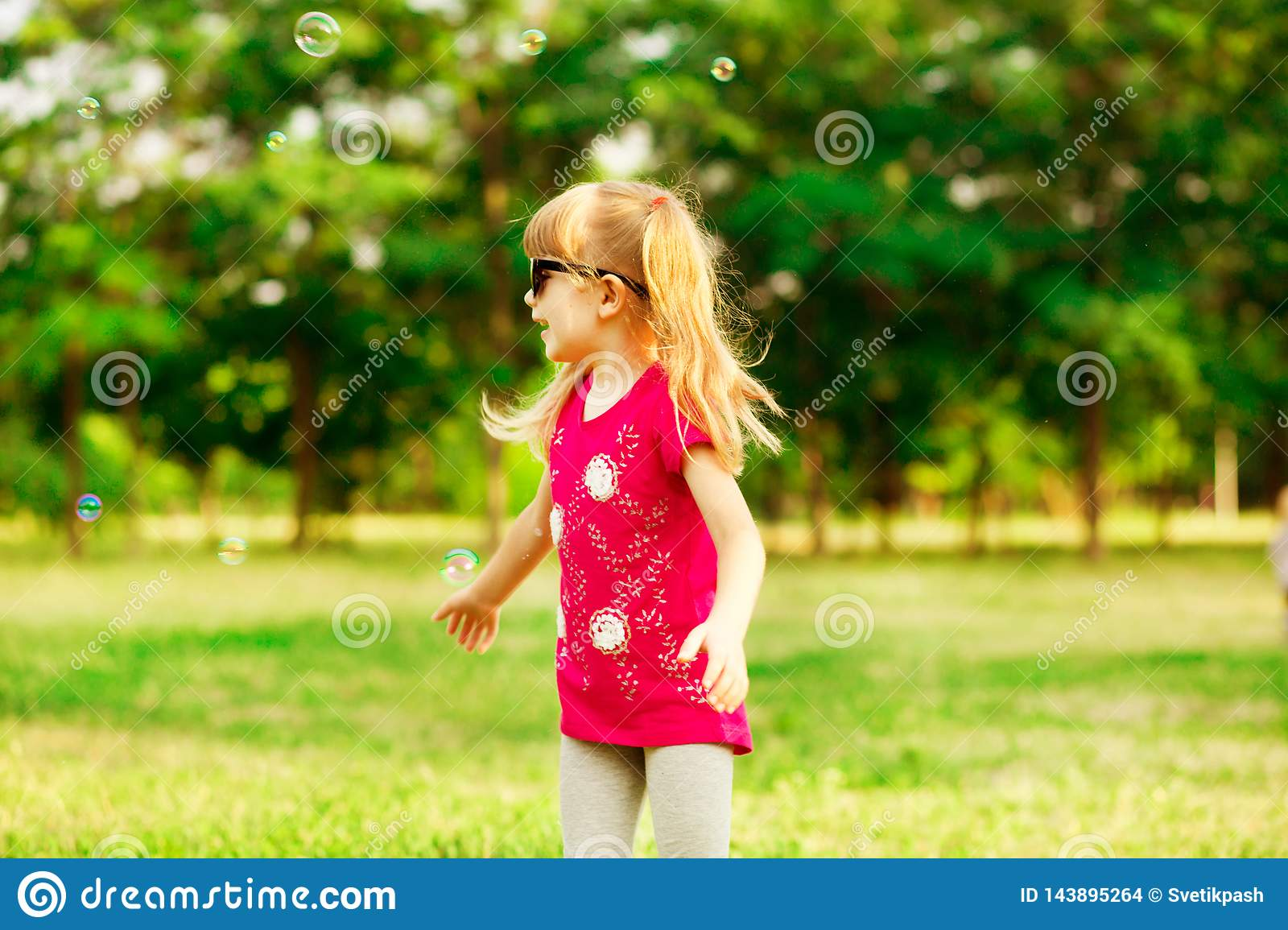 Happy Little Blond Girl Blows Soap Bubbles In Summer Park
