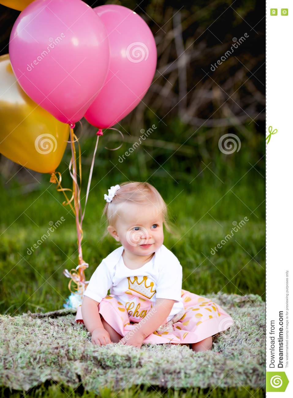 Happy little blonde caucasian girl outside with balloons