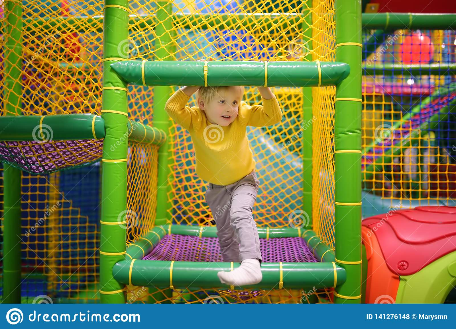 Happy little boy having fun in amusement in play center. Child playing on indoor playground