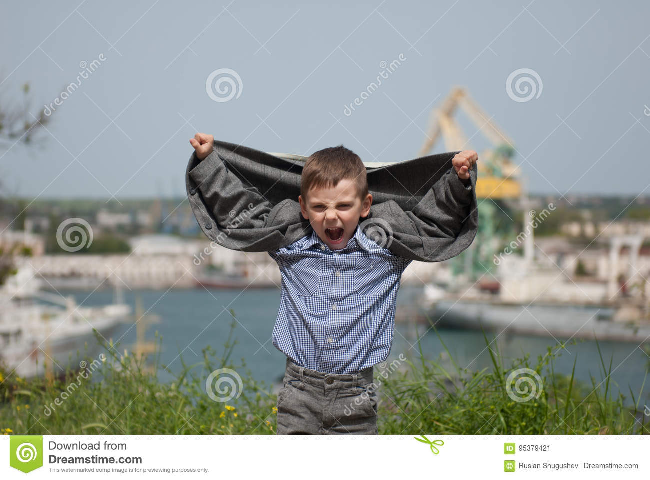 5bb043c366a9e Funny little boy raised his hands up with his jacket like wings on sea port  background