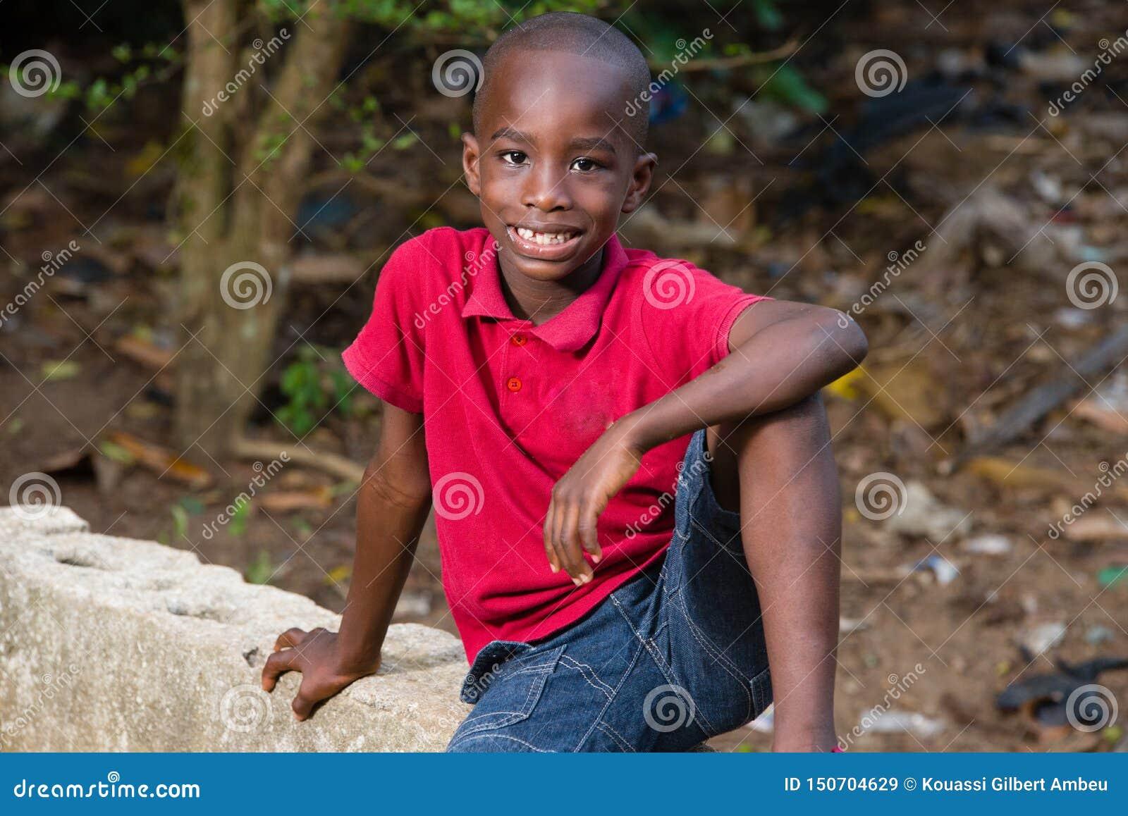 Happy little boy sitting alone outside