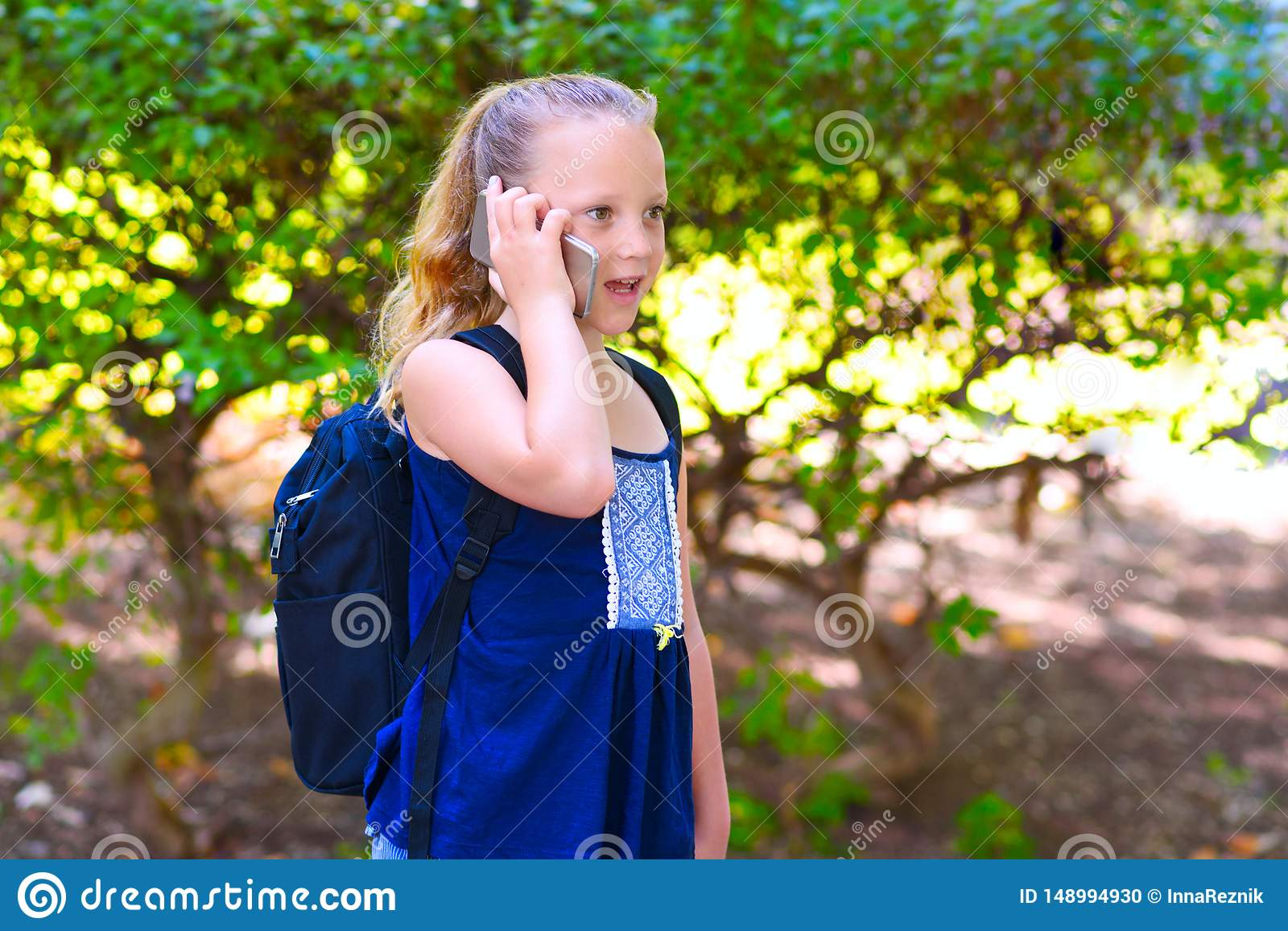 Happy little child girl go to school and talking on mobile phone at city park.