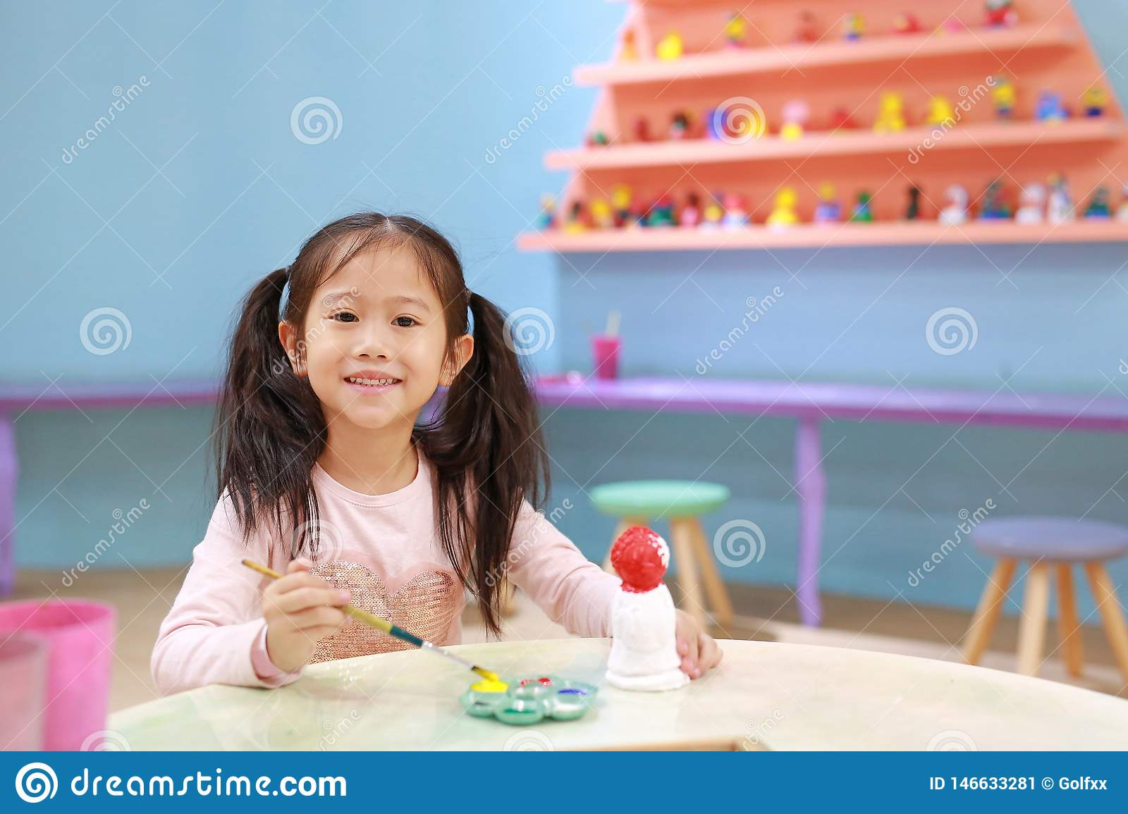 Happy little child girl having fun to paint on stucco doll indoor