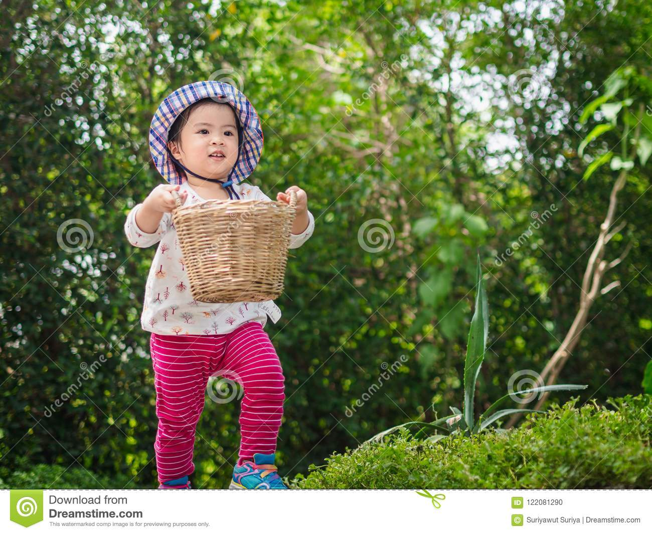 Happy little cute girl holding the basket and runing in the garden. Farm, Happy, Children Concept.